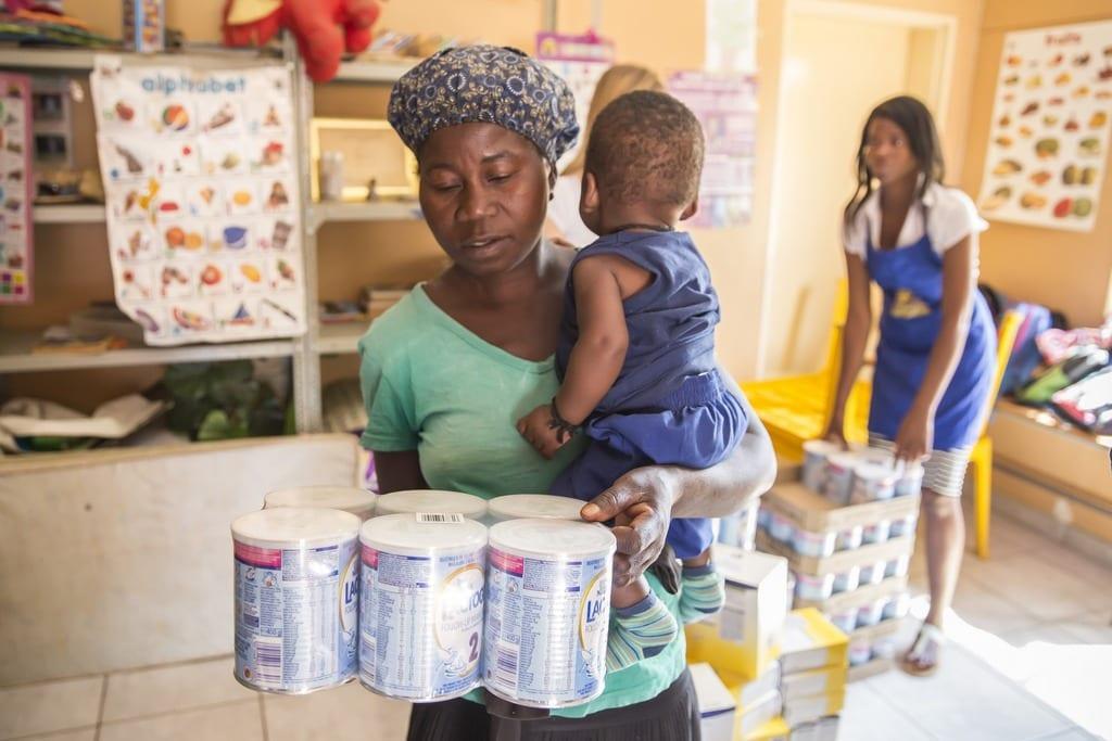 Mutter mit einem Milchpulverpaket